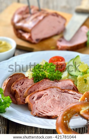 Portion of oven fresh Bavarian meat loaf with potato salad, pretzel and mustard