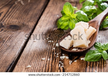 Portion of Parmesan Cheese with Basil on wooden background - stock photo