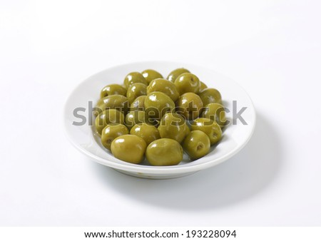 portion of pickled green olives with stones, served on the plate - stock photo