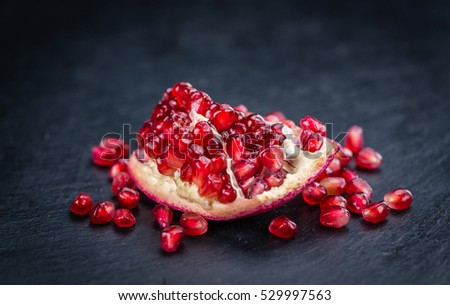 Portion of Pomegranate as detailed close up shot on a slate slab (selective focus)