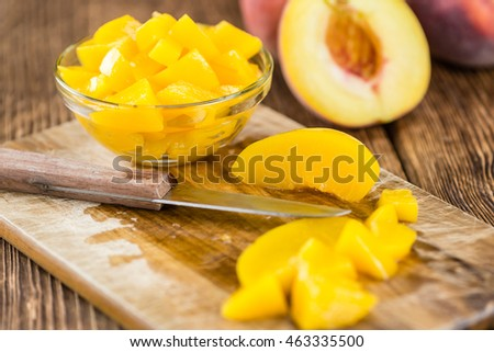 Portion of preserved Peaches (close-up shot) on wooden background