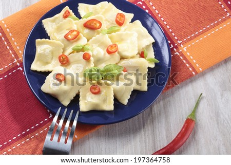 Portion of ravioli with red pepper on a colorful plate - stock photo