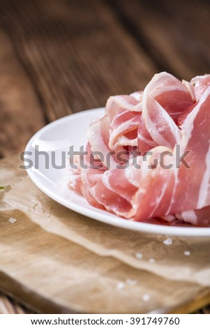 Portion of raw Bacon (close-up shot) on wooden background