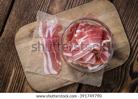 Portion of raw Bacon (close-up shot) on wooden background - stock photo
