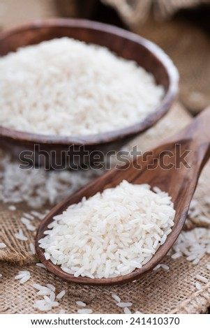 Portion of Rice on rustic wooden background (close-up shot)