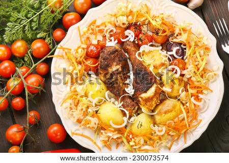 Portion of roasted chicken drumsticks with vegetables in a plate on a wooden background - stock photo