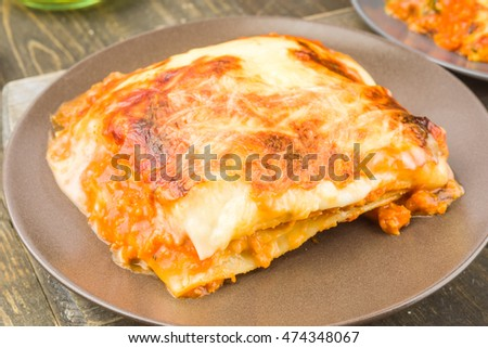 portion of roasted meat lasagna on wooden