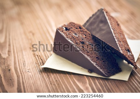 portion of sacher cake on wooden table - stock photo
