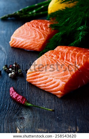 Portion of salmon fillet with aromatic herbs and spices over dark wooden texture - healthy food, diet or cooking concept. - stock photo