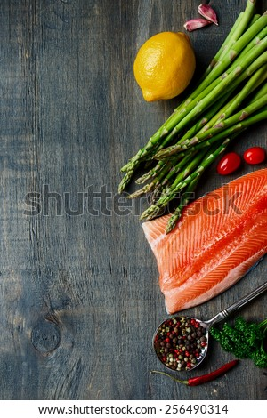 Portion of salmon fillet with asparagus and aromatic herbs, spices and vegetables over wood - healthy food, diet or cooking concept. Top view. - stock photo