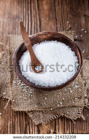Portion of Salt on dark wooden background (close-up shot) - stock photo