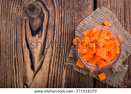Portion of sliced carrot (selective focus) on wooden background - stock photo