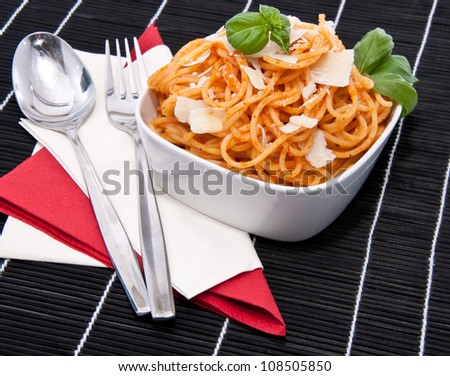 Portion of spaghetti in a bowl with silverware on black tablecloth