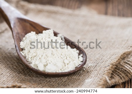 Portion of Spelt Flour (close-up shot) on rustic wooden background