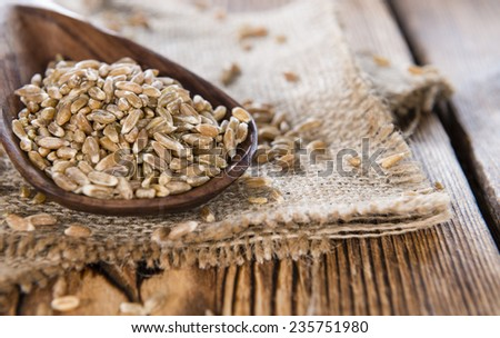 Portion of Spelt on dark wooden background (close-up shot) - stock photo