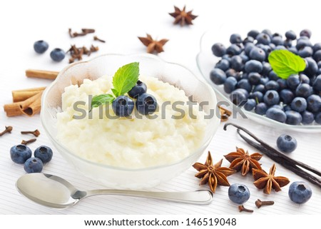 Portion of spicy rice pudding dessert with blueberries - stock photo