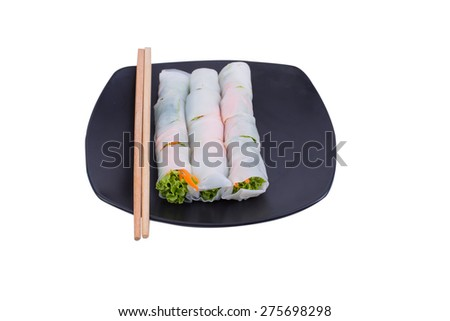 Portion of spring rolls on black dish with spicy sauce, vegetables and in noodle tube