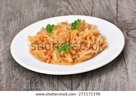 Portion of stew cabbage on white plate over rustic table, close up view - stock photo
