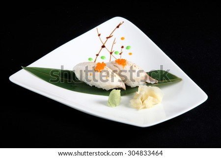 portion of sushi with vegetables on white plate, black background