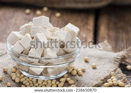 Portion of Tofu (detailed close-up shot) on wooden background - stock photo