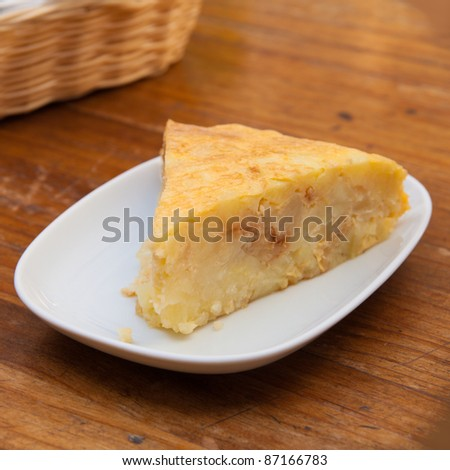 portion of tortilla (Spanish omelette) on a wooden table - stock photo