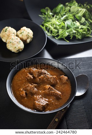 Portion of traditional Beef stew - goulash on wooden table - stock photo