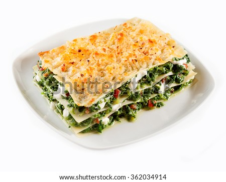 Portion of traditional Italian lasagne with spinach and mozzarella cheese served on a square plate isolated on white, high angle view - stock photo
