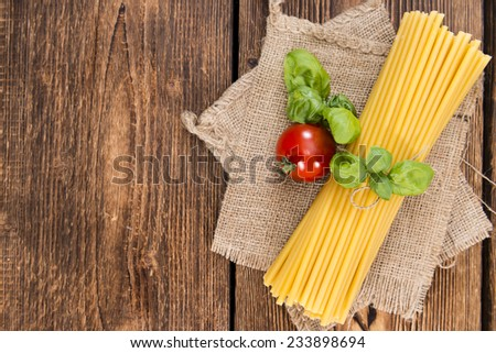 Portion of uncooked Macaroni (detailed close-up shot) on wooden background - stock photo