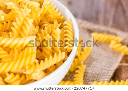 Portion of uncooked Pasta (Fussili) on rustic wooden background
