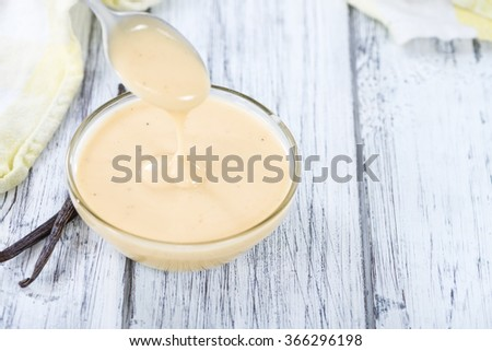 Portion of Vanilla Sauce (close-up shot) on wooden background - stock photo