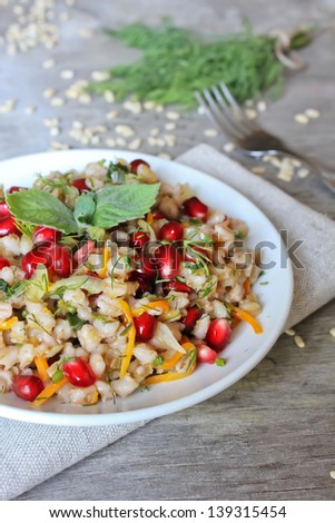 Portion of warm pearl barley salad with carrot and pomegranate seeds in a plate - stock photo