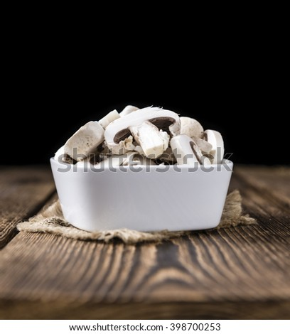 Portion of white Mushrooms (close-up shot) on vintage wooden background