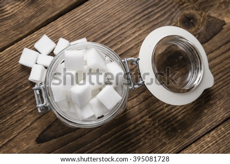Portion of white Sugar (selective focus) on vintage wooden background