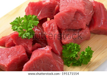 portioned beef shoulder on the wooden cutting board - stock photo