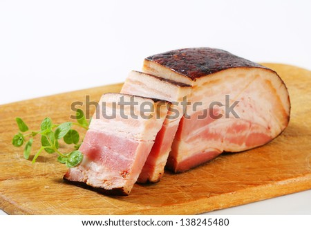 portioned block of bacon on a wooden cutting board - stock photo
