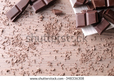 Portions and sparse chocolate chips on a white porcelain container on a brown wooden table. Horizontal composition. Top view - stock photo