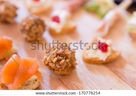 Portions of Hors D'oeuvres on a wooden platter - stock photo