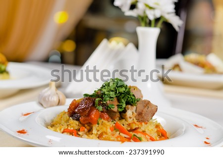 Portions of roast meat on a bed on savory rice with carrots and fresh herbs served at a table in a restaurant, low angle close up view