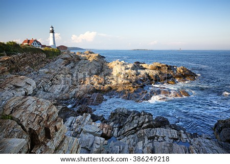 Portland Head lighthouse with the rocky coastline in the foreground.