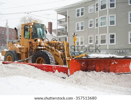 PORTLAND, MAINE, USA - DECEMBER 29, 2015: Snow plow clearing the street in Portland, Maine during a snowstorm. The December 29th storm was the first storm of the unusually warm winter season.