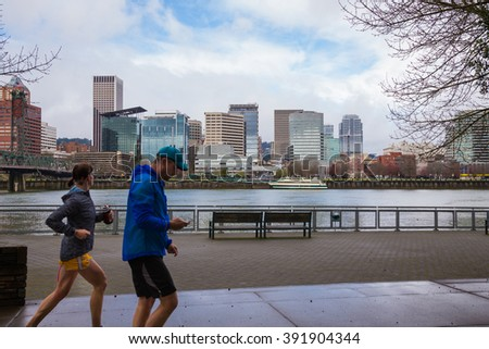 PORTLAND, OR - FEBRUARY 27, 2016: Runners and walkers make use of the waterfront trail system in downtown Portland Oregon. - stock photo
