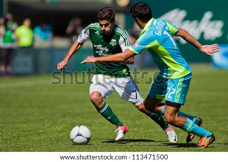 PORTLAND, OR - SEPT 15: The Portland Timbers Sal Zizzo #7 battles for a ball with Leonardo Gonzalez #12 of the Seattle Sounders during the game, on Sep 15, 2012 at Jeld-Wen Field in Portland, OR. - stock photo