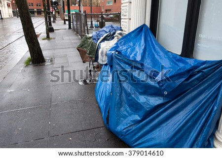 Portland, OR, USA - January 16, 2016: Downtown homeless situation shows people setting up tents on the street. - stock photo