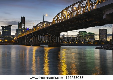 Portland Oregon City Skyline Under Hawthorne Bridge by the Bank of Willamette River at Dusk - stock photo