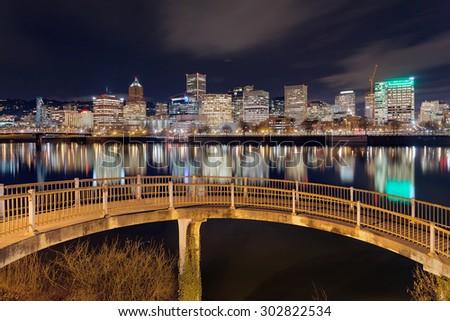 Portland Oregon downtown city skyline from pedestrian bridge along Willamette River at night - stock photo