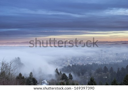 Portland Oregon Downtown Cityscape Covered in Fog and Low Clouds at Sunset with Mount Hood - stock photo
