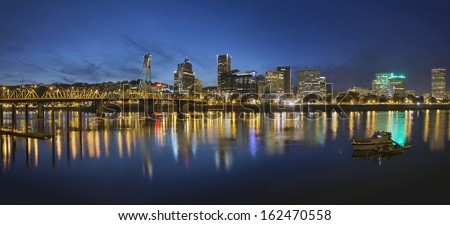 Portland Oregon Downtown Skyline with Hawthorne Bridge Along the Banks of Willamette River at Evening Blue Hour Panorama - stock photo