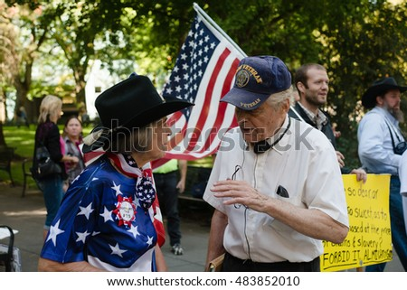PORTLAND, OREGON SEPTEMBER 13 2016, Older protesters of the trial of the armed occupation of the Malheur National Wildlife Refuge, talking to each other. The woman wearing a colorful US flag shirt.