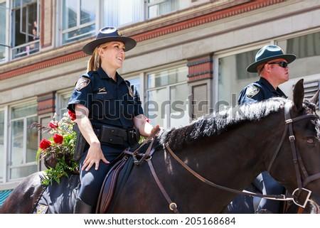 Portland, Oregon, USA - JUNE 7, 2014: Portland Police Mounted Patrol  in Grand floral parade through Portland downtown. - stock photo
