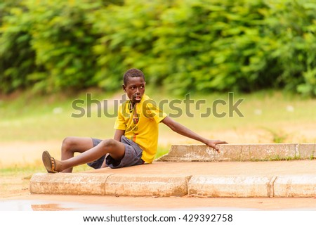 PORTO-NOVO, BENIN - MAR 10, 2012: Unidentified Beninese boy in a Barcelona shirt sits in the street. People of Benin suffer of poverty due to the difficult economic situation